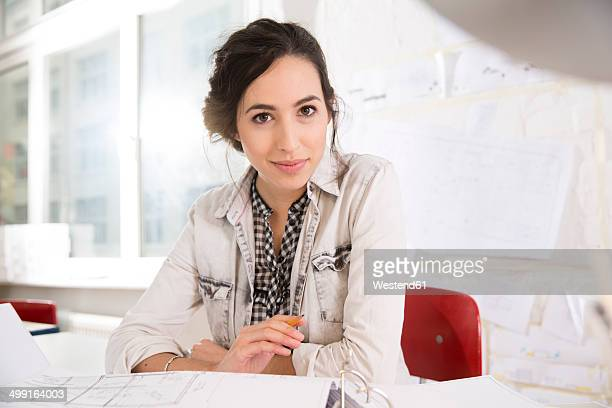 Portrait of young female architect at her desktop in office