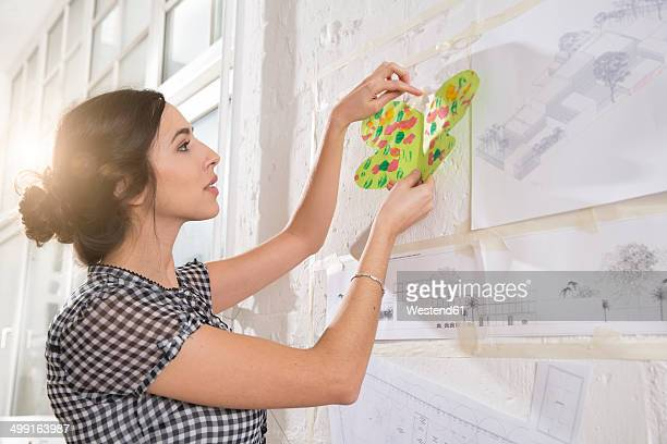 Portrait of young female architect fastening child's painting on pin board