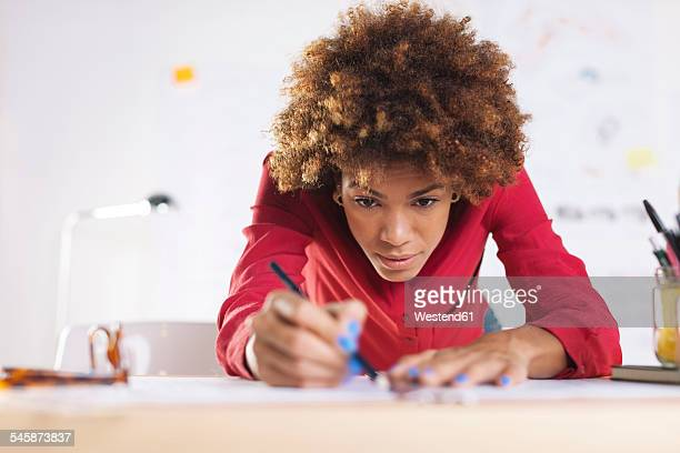 Portrait of young female architect working at her desk