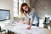 Portrait of young attractive female architect working on project in office