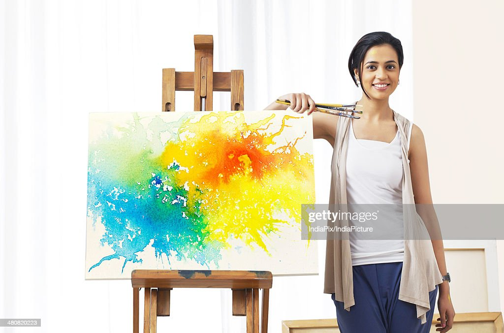 Portrait of young female artist standing by painting at home : Stock Photo