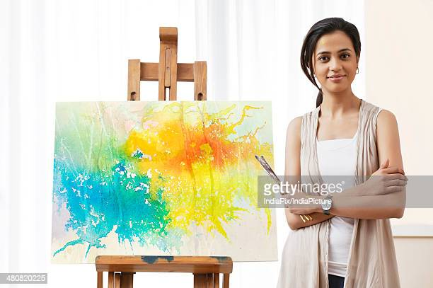 Portrait of young female artist standing by painting at home