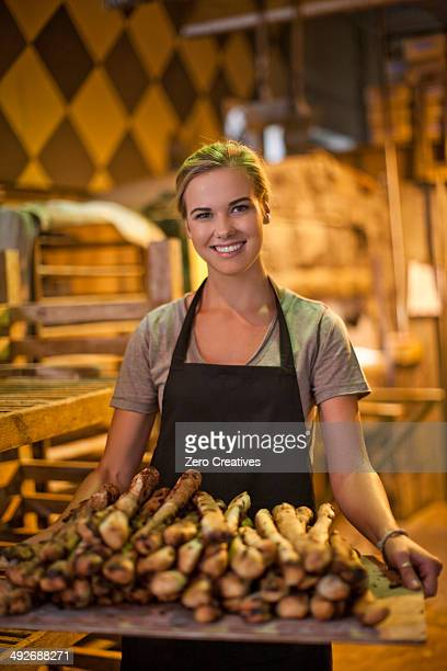 Portrait of young female baker carrying a tray of breadsticks