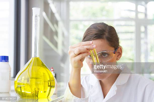 Portrait of young female chemist holding glass tube with yellow reagent