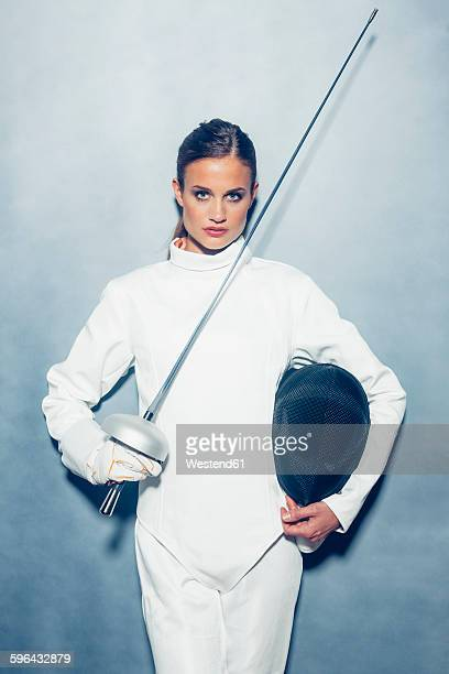 Portrait of young female fencer with weapon