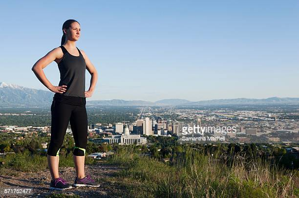 Portrait of young female runner on dirt track above city in valley