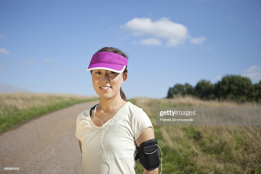 Portrait of young female runner on dirt track : Stock Photo
