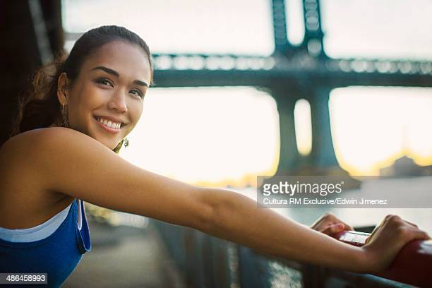 Portrait of young female runner stretching, New York City, USA