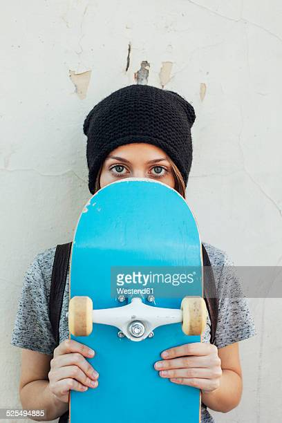 Portrait of young female skate boarder holding hiding behind her skateboard