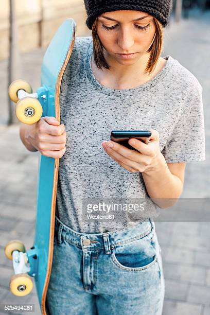 Portrait of young female skate boarder using smartphone