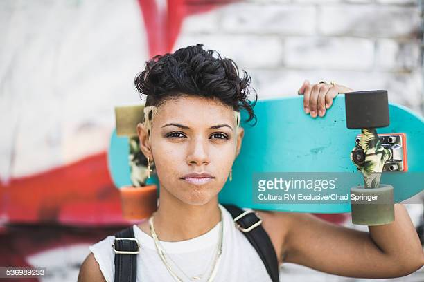 Portrait of young female skateboarder and graffiti wall