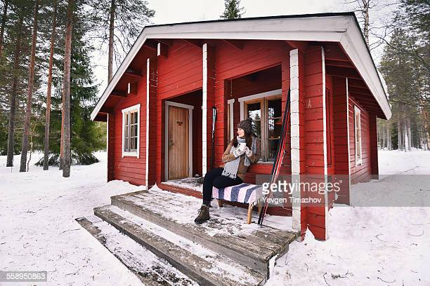 Portrait of young female skier drinking coffee on cabin porch, Posio, Lapland, Finland