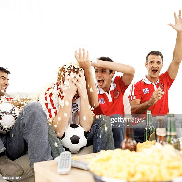 portrait of young footballs fans enjoying the game with beer and popcorn