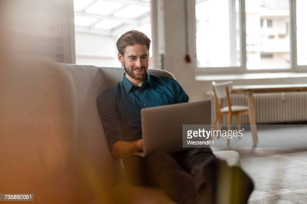 Portrait of young freelancer sitting on couch in a loft using laptop