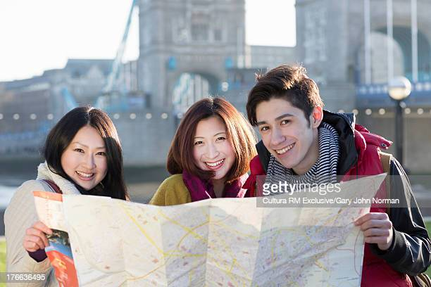 Portrait of young friends holding map by Tower Bridge, London, England