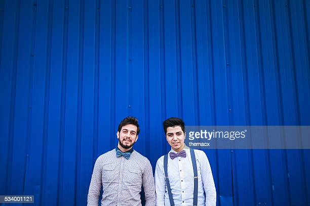 Portrait of young gay couple on blue
