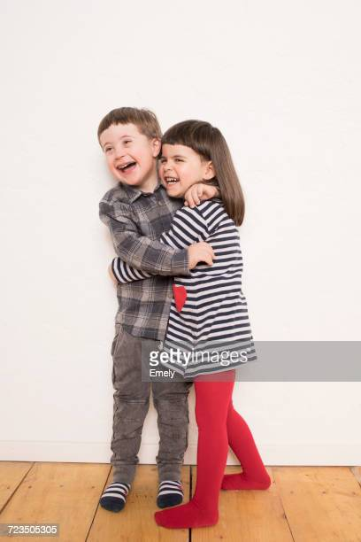 Portrait of young girl and boy, hugging, laughing