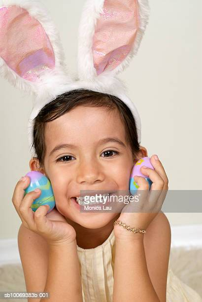 Portrait of young girl (4-5) as easter bunny, holding eggs