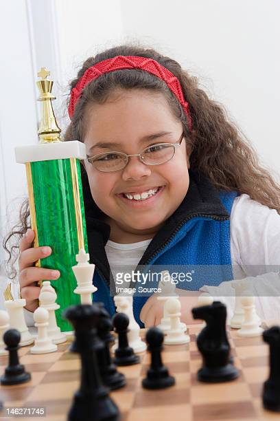 Portrait of young girl holding chess trophy