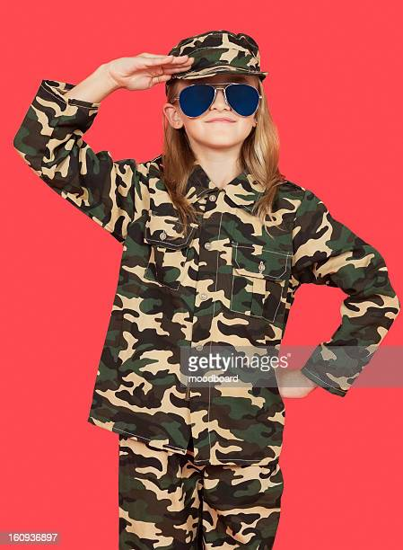 Portrait of young girl in military uniform saluting against red background