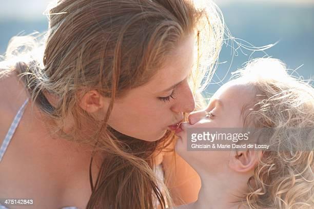 Portrait of young girl kissing older sister