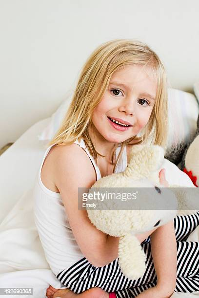 Portrait of young girl kneeling on bed with soft toy