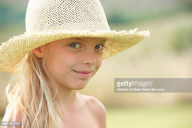 Portrait of young girl outdoors, wearing straw hat