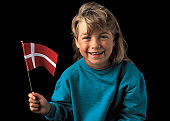 Portrait of young girl (6-8) smiling holding the flag of Denmark