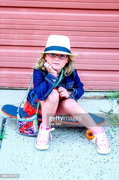 Portrait of young girl wearing tutu, denim jacket and hat, sitting on skateboard