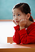 Portrait of young girl with hands on her face looking up