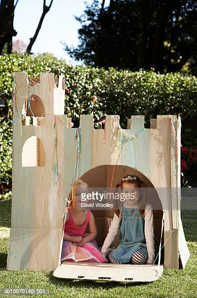 Portrait of young girls (12-17 months) sitting in cardboard castle