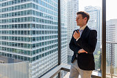 Portrait of young handsome businessman standing against glass window with view of the city horizontal shot