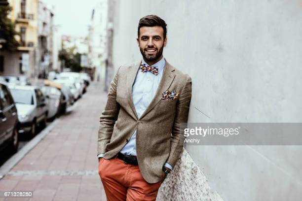 Portrait of young handsome fashion blogger leaned on the wall.