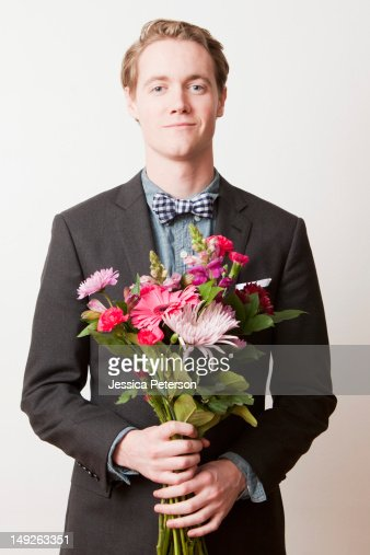 Portrait of young handsome man holding bunch of flowers