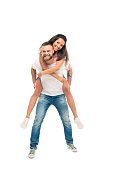'portrait of young happy couple, man piggybacking woman, isolated on white