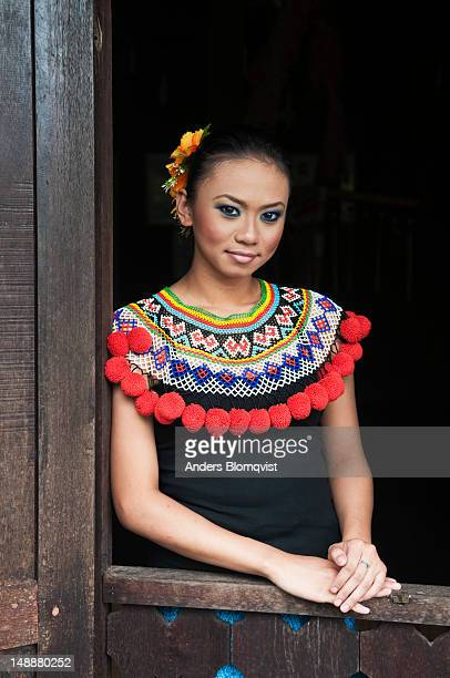 Portrait of young Iban tribal girl standing in longhouse window at Sarawak Cultural Village near Kuching.