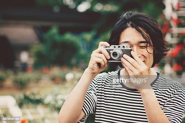 Retrato de jovem homem japonês com retro de máquina