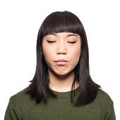 Portrait of young japanese woman standing with her eyes closed against white background
