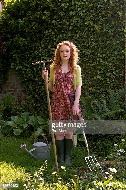 portrait of young lady holding garden tools.