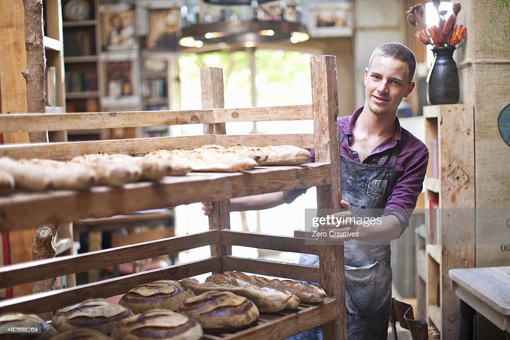 Portrait of young male baker with shelves of fresh bread