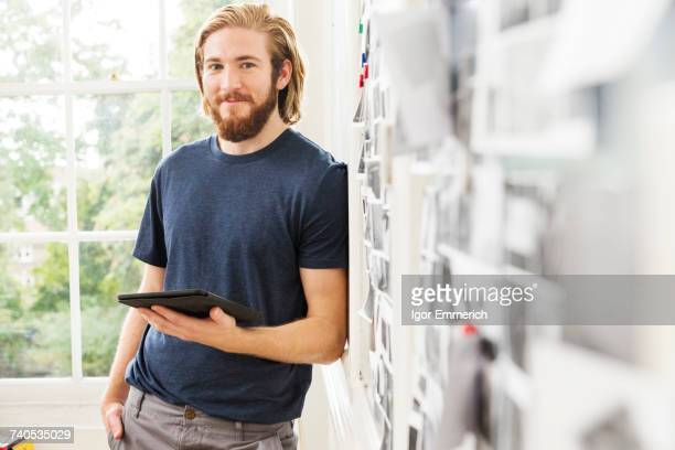 Portrait of young male designer leaning against mood board in creative studio