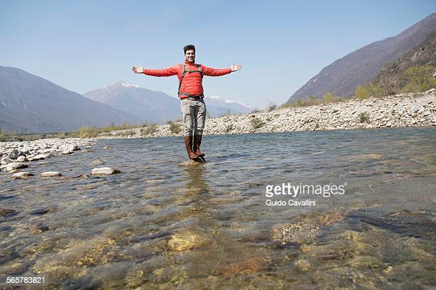 Portrait of young male hiker standing on Toce river rock, Vogogna, Verbania, Piemonte, Italy