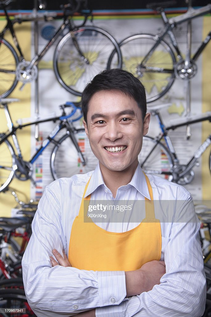 Portrait of young male mechanic in bicycle store, Beijing : Stock Photo