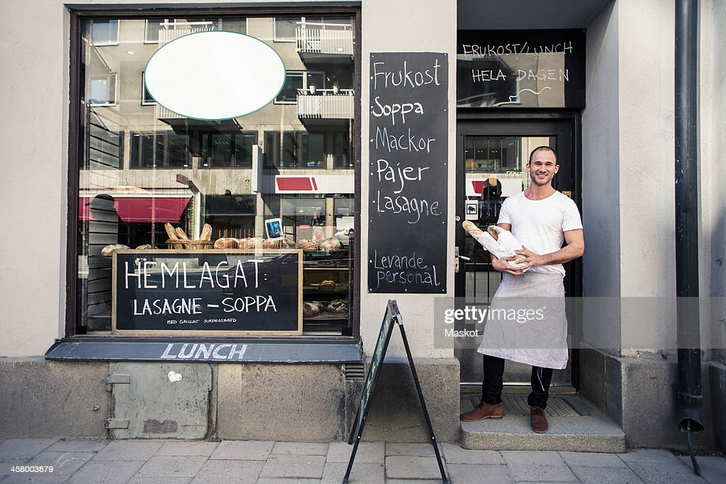 Portrait of young male owner holding bread loafs while standing outside bakery