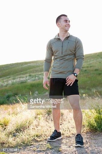 Portrait of young male runner on hillside