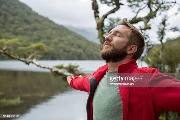 Portrait de jeune homme bras tendus par montagne Lac