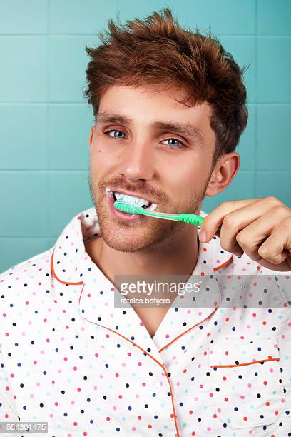 Portrait of young man brushing his teeth
