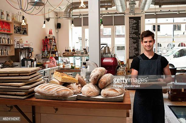 Portrait of young man carrying tray in cafe