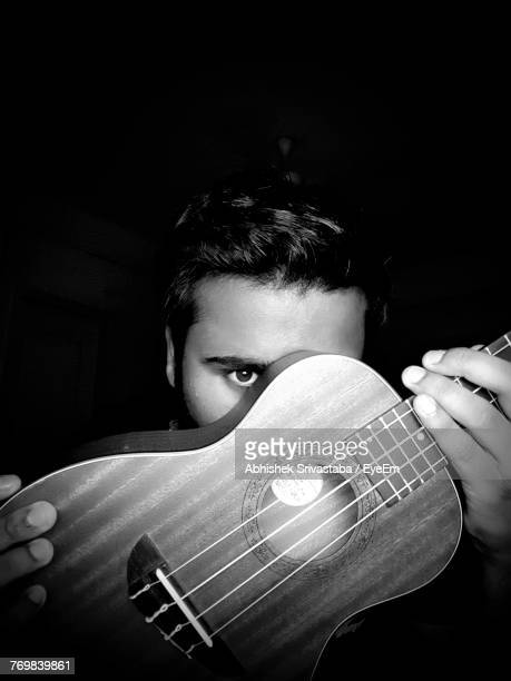 Portrait Of Young Man Covering Face With Ukulele Against Black Background