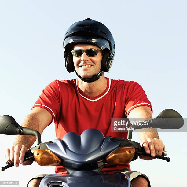 Portrait of young man driving motor bike wearing helmet